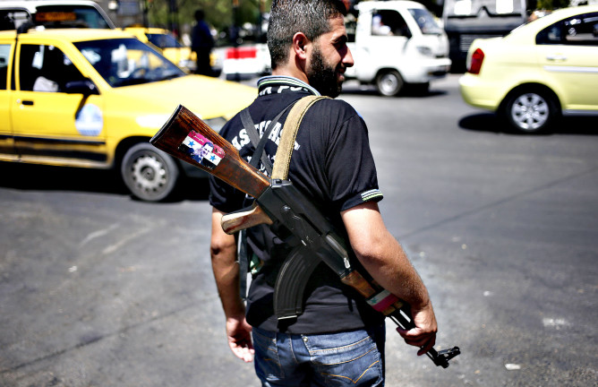 A Syrian military soldier holds his Ak-47 with a sticker of Syri